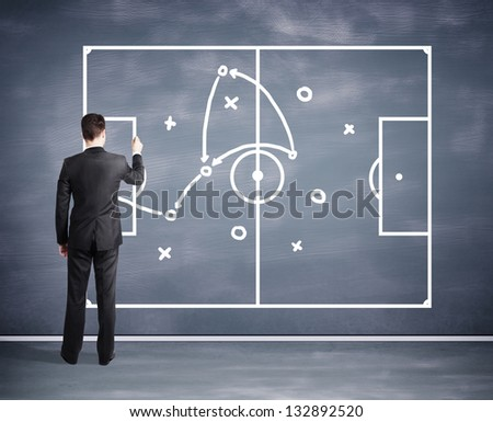 man drawing tactic scheme on big black desk board - stock photo
