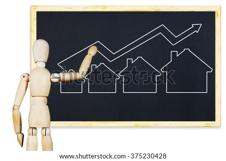 Man draws a graph of real estate sales growth on a blackboard. Abstract image with wooden puppet - stock photo
