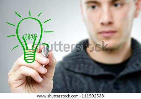 Man draws a green bulb - renewable energy concept - stock photo