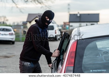 Man dressed in black with a balaclava on his head entering the vehicle and stealing a car. Car thief, car theft concept - stock photo
