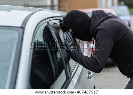 Man dressed in black with a balaclava on his head looking through car window and wondering how to break into this car. Car thief, car theft concept