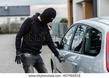Man dressed in black with a balaclava on his head pulls the handle of a car. Car thief, car theft concept - stock photo