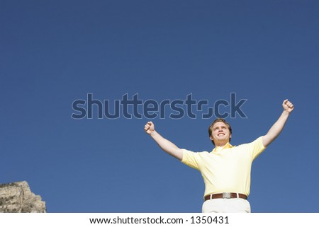 Man dressed in casual clothes with his arms raised under a blue sky