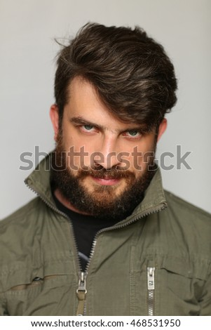 Man dressed in khaki jacket with interesting look. Close.up. Gray