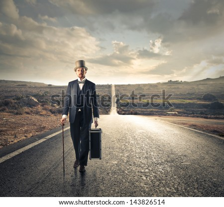 man dressed in old clothes walking on the road - stock photo