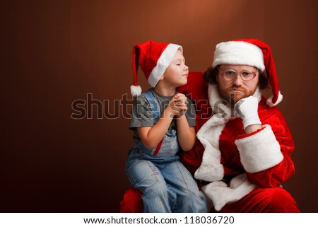 Man,dressed in Santa costume looks tired and unhappy Boy is  sitting on Santas knee and asking about his  present.  Brown background,copyspace - stock photo