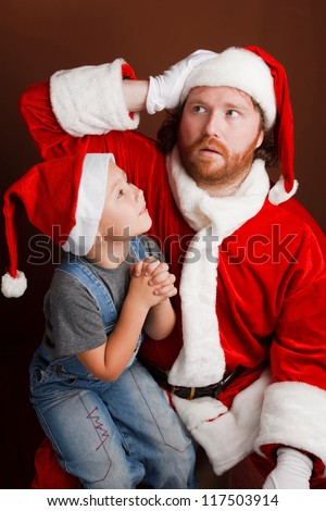 Man,dressed in Santa costume looks tired and unhappy Boy is  sitting on Santas knee and sharing his Christmas wishes