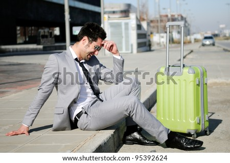 Man dressed in suit and suitcase sitting on the floor in the street