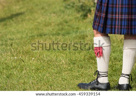 Man dressed in traditional Tartan Kilt an example of Scotlands national costume