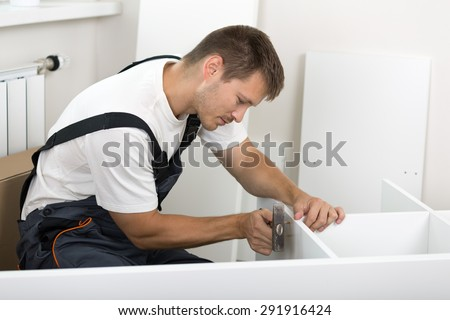 Man dressed in workers' overall assembing furniture in new home. DIY, home and moving concept - stock photo