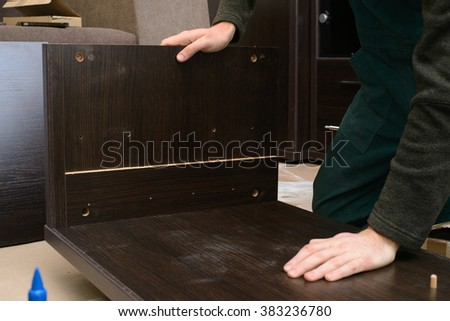 Man dressed in workers' overall assembling furniture sitting on the floor in new home. home and moving concept - stock photo