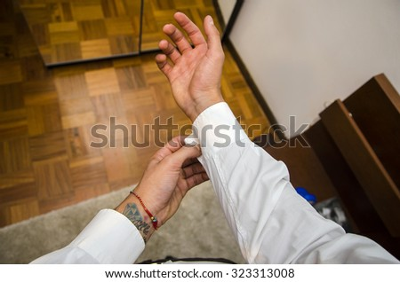 Man dressing standing in bedroom, dressing, fixing shirt cuffs, first person point of view. Self POV - stock photo