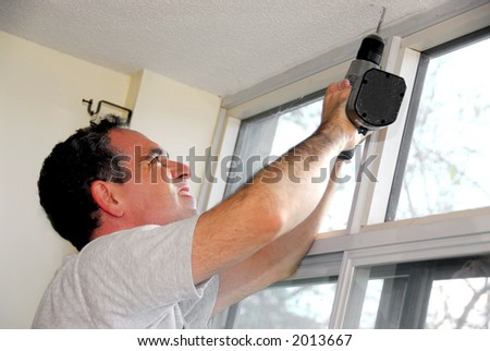 Man drilling a hole in a ceiling - stock photo