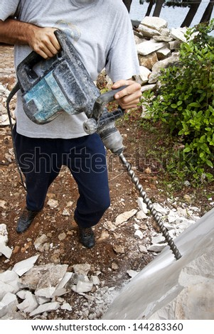 Man drills holes with drilling machine in stone block - stock photo
