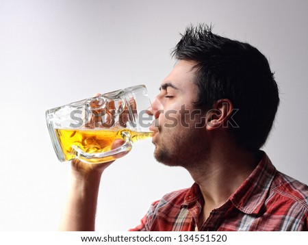 Man drinking a glass of beer - stock photo
