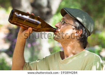 Man drinking beer from bottle outdoors. - stock photo