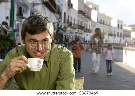 man drinking cappuccino with family in the background - stock photo