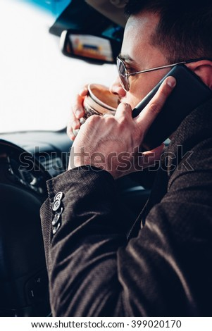 Man drinking coffee and using mobile phone while driving car with copy space - stock photo