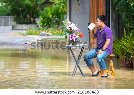 Man drinking coffee around the home during flooded home and vehicle. Can't to do every things them relax by self on flood situation. - stock photo