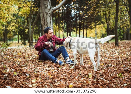 man drinking coffee in park and playing with labrador dog
