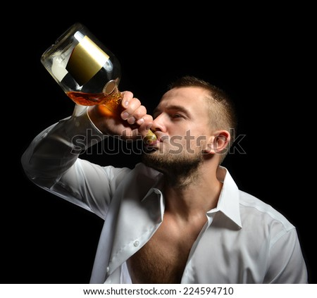 Man drinking cognac alcohol whiskey from the bottle on a black background - stock photo