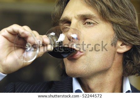 man drinking glass of red wine - stock photo