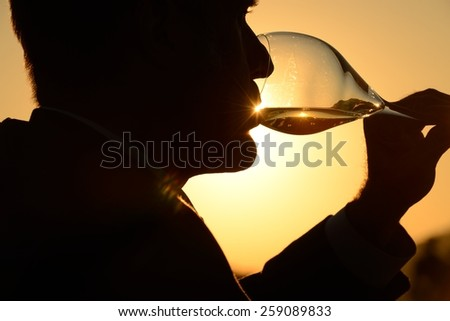man drinking glass of wine at sunset