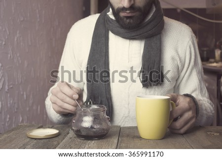 man drinking tea and eating a jam - stock photo