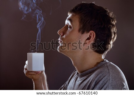 Man drinking warm beverage. Low key image. - stock photo
