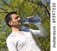 man drinking water after sport in a park - stock photo