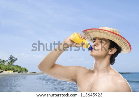 Man drinking water from a water bottle on the beach