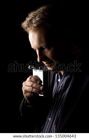 man drinks from flask