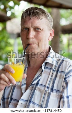 man drinks orange juice in summer cafe - stock photo