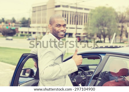 Man driver happy smiling showing thumbs up opening door of a sports blue car isolated outside parking lot city background. Handsome young man excited about his new vehicle. Positive face expression - stock photo