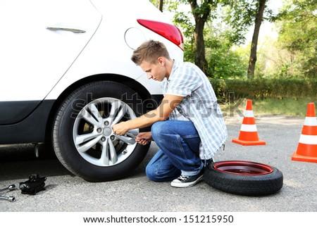Man driver having trouble at road changing wheel - stock photo