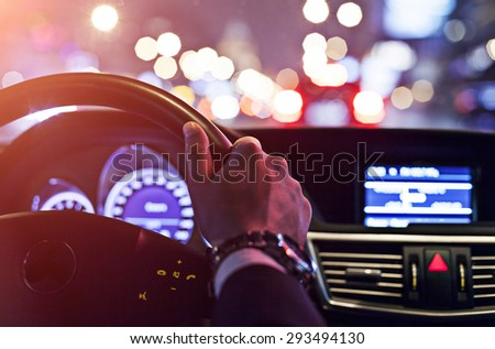 man driving a car at night - stock photo