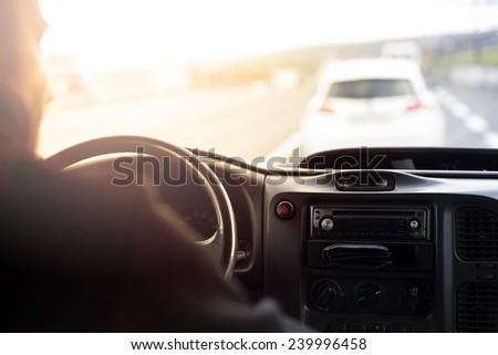 Man driving a car at sunset - stock photo