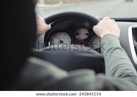 Man driving a car. Hands on steering wheel of a car. - stock photo