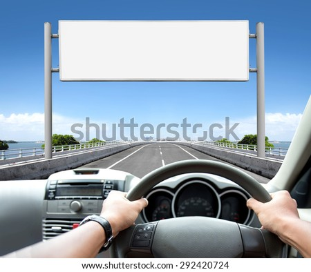 Man driving a car while looking at billboard or road sign ahead - stock photo