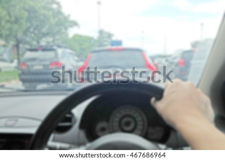 man driving a car with his hands on the steering wheel blur background