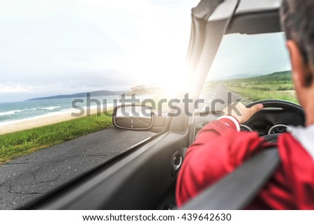 Man driving a convertible car on the country road by the sea. View from the inside behind the driver.