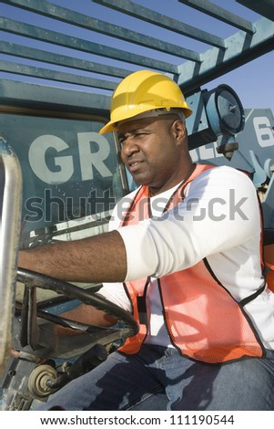 Man driving a forklift truck at a construction site - stock photo