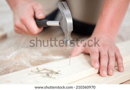 Man driving a nail during renovation, horizontal - stock photo