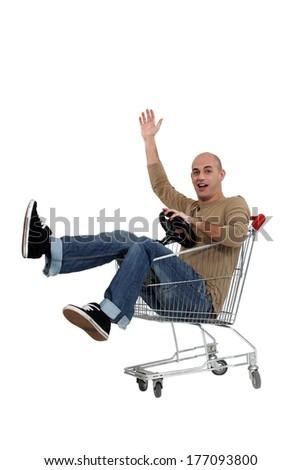 man driving a shopping cart - stock photo