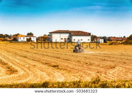 man driving a small tractor plowing a large field in the countryside of Romagna in Italy