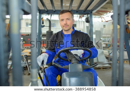 man driving an elevator in the warehouse - stock photo