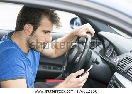 Man driving and looking message in his smart phone. - stock photo