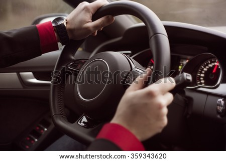 Man driving car. Closeup of hands on a steering wheel. Lifestyle - stock photo