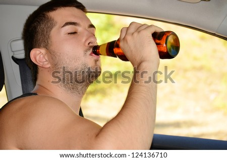 man driving car with beer in hand - stock photo