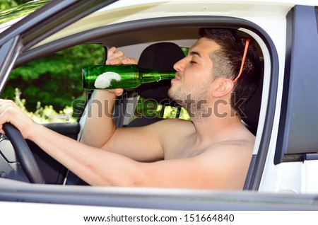 man driving car with beer in hand